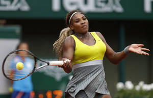 Photo - Serena Williams of the U.S, returns the ball to France's Alize Lim during the first round match of  the French Open tennis tournament at the Roland Garros stadium, in Paris, France, Sunday, May 25, 2014. Williams won 6-2, 6-1. (AP Photo/Darko Vojinovic)