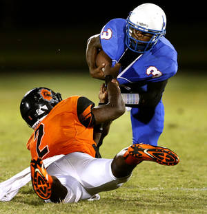 Photo - Douglass' Deondre Clark tackles Millwood's Cameron Batson for a loss at the All City Football Preview at Douglass High School on Friday, Aug. 30, 2013 in Oklahoma City, Okla.  Photo by Steve Sisney, The Oklahoman