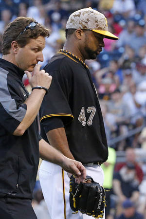 Photo - ADDS WHY LIRIANO LEFT THE GAME - Pittsburgh Pirates' Francisco Liriano (47) leaves the game with a team trainer during the fourth inning of a baseball game against the Chicago Cubs in Pittsburgh Tuesday, June 10, 2014.  Liriano left his start in the top of the fourth inning Tuesday night with what the Pirates said was discomfort in his left side.   (AP Photo/Gene J. Puskar)