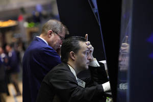photo -   Trader Theodore Nelson, right, is reflected on a panel as he works on the floor of the New York Stock Exchange Monday, June 4, 2012. The Dow Jones industrial average opened at its lowest level since December after a 275-point sell-off on Friday caused by grim economic signals, especially a dismal report on the U.S. labor market. (AP Photo/Richard Drew)