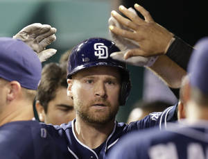 Photo - San Diego Padres' Chase Headley is congratulated in the dugout after hitting a solo home run off Cincinnati Reds relief pitcher Aroldis Chapman in the ninth inning of a baseball game, Tuesday, May 13, 2014, in Cincinnati. San Diego won 2-1. (AP Photo)