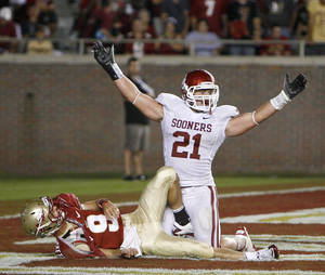 Photo - Oklahoma's Tom Wort (21) reacts after hitting Florida's Clint Trickett (9) during a college football game between the University of Oklahoma (OU) and Florida State (FSU) at Doak Campbell Stadium in Tallahassee, Fla., Saturday, Sept. 17, 2011. Photo by Bryan Terry, The Oklahoman