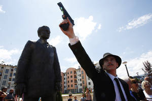 Photo - Bosnian actor Jovan Mojsilovic poses with a plastic replica gun  during ceremony of unveiling statue of Gavrilo Princip in Istocno Sarajevo, on Friday, June 27, 2014. Marking the centennial of the beginning of World War I in their own way, Bosnian Serbs have unveiled a monument of Gavrilo Princip in the Eastern part of Sarajevo to the man who ignited the war by assassinating the Austro-Hungarian crown prince on June 28, 1914.(AP Photo/Amel Emric)