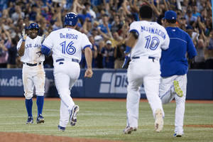 Photo - Toronto Blue Jays' Rajai Davis, left, turns to celebrate with on rushing teammates after hitting a game-winning single during the ninth inning against Baltimore Orioles baseball game in Toronto on Friday June 21, 2013. (AP Photo/The Canadian Press, Chris Young)