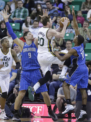 Photo - Utah Jazz's Gordon Hayward (20) goes to the basket as Orlando Magic's Nikola Vucevic (9), of Montenegro, and Ronnie Price (10) defend in the second quarter during an NBA basketball game on Saturday, March 22, 2014, in Salt Lake City. (AP Photo/Rick Bowmer)