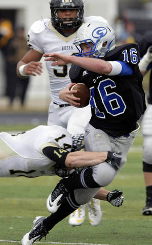 Photo - CLASS 5A HIGH SCHOOL FOOTBALL PLAYOFFS: McAlester's Adam Boyd tackles Guthrie quarterback Bryan Dutton as Devin Rolan chases in the 2nd half of their 5A semifinal game at Sapulpa, OK, Nov. 26, 2011. MICHAEL WYKE/Tulsa World ORG XMIT: DTI1111261921322138