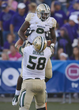 Photo - Baylor running back Glasco Martin gets a lift from offensive linesman Spencer Drango during Saturday's game at Kansas State. AP photo
