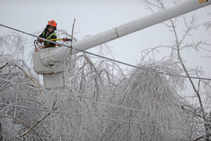 Photo - Andrew Powers, an arborist with Asplundh Tree Experts, clears iced branches from power lines along Mayflower Heights Drive in Waterville, Maine, on Monday, Dec. 23, 2013. Central Maine Power said nearly 57,000 were without power Monday afternoon, up from 29,000 it had been reporting earlier. Hardest hit was Kennebec County with about 20,000 and Waldo County at nearly 15,000 customers without power.  (AP Photo/Morning Sentinel, Michael G. Seamans)