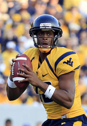photo - West Virginia quarterback Geno Smith (12) looks to pass during the second quarter of their NCAA college football game against Kansas in Morgantown, W.Va., on Saturday, Dec. 1, 2012. (AP Photo/Christopher Jackson)