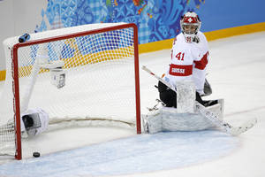 Photo - Goalkeeper Florence Schelling of Switzerland looks back at the puck after Jenni Hiirikoski's of Finland scored during the first period of the 2014 Winter Olympics women's ice hockey game at Shayba Arena, Wednesday, Feb. 12, 2014, in Sochi, Russia. (AP Photo/Petr David Josek)