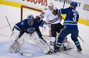 Photo - Vancouver Canucks defenceman Kevin Bieksa (3) tries to clear Chicago Blackhawks center Andrew Shaw (65) from in front of Vancouver Canucks goalie Roberto Luongo (1) during the third period of NHL action in Vancouver, British Columbia Wednesday, Jan. 29, 2014. (AP Photo/The Canadian Press, Jonathan Hayward)