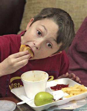 Photo -      Fifth-grader Chase Crutchfield eats a sandwich during Reading Club at Stanley Hupfeld Academy on Thursday. Photo by David McDaniel, The Oklahoman  <strong>David McDaniel -  The Oklahoman </strong>