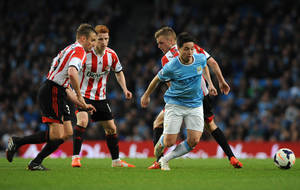 Photo - Manchester City's Samir Nasri, right, evades Sunderland's Andrea Dossena, left, Jack Colback and Sebastian Larsson during the English Premier League soccer match between Manchester City and Sunderland at The Etihad Stadium, Manchester, England, Wednesday, April 16, 2014. (AP Photo/Rui Vieira)