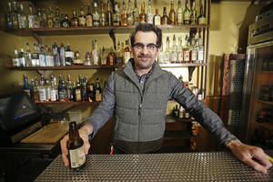 "Photo - In this April 16, 2014 photo, actor Ty Burrell, who plays bumbling dad Phil Dunphy on ABC's ""Modern Family,"" poses holding a beer at Bar X, the cocktail bar he co-owns, in Salt Lake City. Burrell just opened Beer Bar, a beer garden-like eatery next door to Bar X that serves 150 beers paired up with an array of house-made bratwursts, local breads and Belgian fries. The restaurant sports long tables and benches with high ceilings to evoke that Bavarian beer hall feel. (AP Photo/Rick Bowmer)"