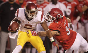 Photo -   Southern California wide receiver Robert Woods (2) carries the ball as he breaks a tackle from Utah linebacker Trevor Reilly (9) in the first quarter during an NCAA college football game Thursday, Oct. 4, 2012, in Salt Lake City. (AP Photo/Rick Bowmer)