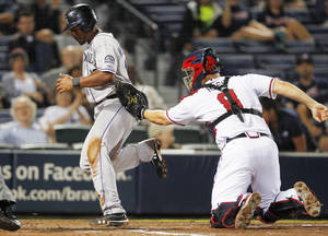 Photo -   Colorado Rockies' Chris Nelson, left, scores on a hit by DJ LeMahieu as Atlanta Braves catcher David Ross (8) can't hang on to the ball in the eighth inning of a baseball game Tuesday, Sept. 4, 2012, in Atlanta. (AP Photo/John Bazemore)