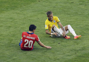 Photo - Brazil's Neymar grimaces after being tackled by Chile's Charles Aranguiz during the World Cup round of 16 soccer match between Brazil and Chile at the Mineirao Stadium in Belo Horizonte, Brazil, Saturday, June 28, 2014. (AP Photo/Hassan Ammar)