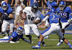 photo -   Rice running back Charles Ross (28) runs through a group of Kansas defenders during the first half of an NCAA college football game, Saturday, Sept. 8, 2012, in Lawrence, Kan. (AP Photo/Charlie Riedel)