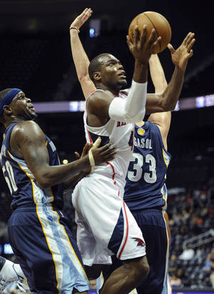 Photo - Atlanta Hawks forward Paul Millsap, center, shoots through the defense of Memphis Grizzlies forward Zach Randolph, left, and center Marc Gasol (33), of Spain, during the first half of an NBA  preseason basketball game, Sunday, Oct. 20, 2013, in Atlanta. (AP Photo/ John Amis)