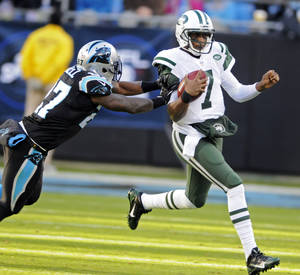 Photo - New York Jets quarterback Geno Smith (7) is pushed out of bounds by Carolina Panthers' Quintin Mikell (27) during the first half of an NFL football game in Charlotte, N.C., Sunday, Dec. 15, 2013. (AP Photo/Mike McCarn)