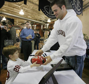 photo - Enid's Austin Box gives an autographed football to Maddux Mayberry after Box signed his letter of intent to play football with the University of Oklahoma on Wednesday, Feb. 7, 2007, in Enid, Okla.     by Chris Landsberger, The Oklahoman