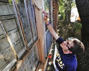 Photo - Cameron Golshani, a University of Central Oklahoma freshman from Edmond, paints wood trim on a house. Golshani was participating with some of his Sigma Tau fraternity brothers in a Rebuilding Together OKC activity. Photo by Jim Beckel, The Oklahoman. <strong>Jim Beckel</strong>