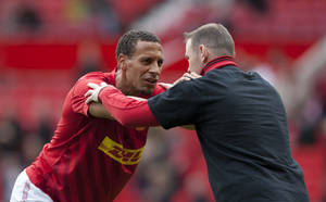 Photo -   Manchester United's Rio Ferdinand, left, and fellow team member Wayne Rooney warm up before their English Premier League soccer match against Stoke at Old Trafford Stadium, Manchester, England, Saturday, Oct. 20, 2012. (AP Photo/Jon Super)