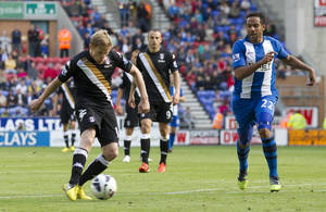 Photo -   Fulham's Damien Duff, left, scores past Wigan Athletic's Jean Beausejour during their English Premier League soccer match at The DW Stadium, Wigan, England, Saturday, Sept. 22, 2012. (AP Photo/Jon Super)