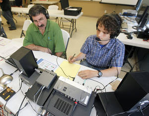 Photo - Karl Kueteman, left, and Joseph Thomas attempt to contact a radio operator in another part of the country, as the Edmond Amateur Radio Society demonstrates the use of amateur radio at Oak Cliff Fire Station in Edmond, OK, Saturday, June 22, 2013,  Photo by Paul Hellstern, The Oklahoman