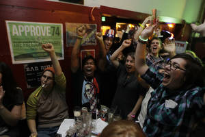 Photo -   Supporters of President Barack Obama, react to news reports of his projected re-election, Tuesday, Nov. 6, 2012, at a bar in Seattle's Capitol Hill neighborhood. (AP Photo/Ted S. Warren)