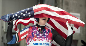 Photo - Erin Hamlin of the United States celebrates with the American flag after finishing her final run to win the bronze medal in the women's singles luge competition at the 2014 Winter Olympics, Tuesday, Feb. 11, 2014, in Krasnaya Polyana, Russia. (AP Photo/The Canadian Press, Jonathan Hayward)