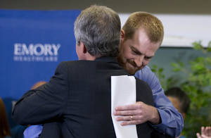Photo - Ebola victim Dr. Kent Brantly, right, hugs a member of the medical staff that treated him, after being released from Emory University Hospital Thursday, Aug. 21, 2014, in Atlanta. Another American aid worker, Nancy Writebol, who was also infected with the Ebola virus, was released from the hospital Tuesday. (AP Photo/John Bazemore)