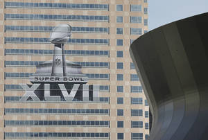 photo - FILE - The NFL Super Bowl XLVII NFL football game logo is seen past the Mercedes-Benz Superdome on the face of an office building as preparations take place in this Sunday, Jan. 27, 2013 file photo taken in New Orleans. New Orleans has celebrated plenty of milestones on its slow road to recovery from Hurricane Katrina, but arguably none is bigger than hosting its first Super Bowl since the 2005 storm left the city in shambles. The Baltimore Ravens and San Francisco 49ers are scheduled to play in Super Bowl XLVII on Sunday, Feb. 3. (AP Photo/Patrick Semansky, File)