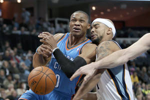 Photo - Oklahoma City Thunder's Russell Westbrook (0) is fouled by Memphis Grizzlies' Jerryd Bayless, right, in the first half of an NBA basketball game in Memphis, Tenn., Wednesday, Dec. 11, 2013. (AP Photo/Danny Johnston)