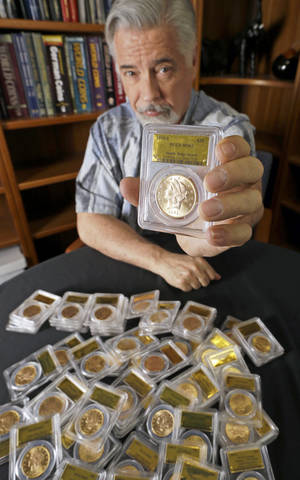 Photo - David Hall, co-founder of Professional Coin Grading Service, poses with some of 1,427 Gold-Rush era U.S. gold coins, at his office in Santa Ana, Calif., Tuesday, Feb. 25, 2014.  A California couple out walking their dog on their property stumbled across the modern-day bonanza: $10 million in rare, mint-condition gold coins buried in the shadow of an old tree. Nearly all of the 1,427 coins, dating from 1847 to 1894, are in uncirculated, mint condition, said Hall, who recently authenticated them. Although the face value of the gold pieces only adds up to about $27,000, some of them are so rare that coin experts say they could fetch nearly $1 million apiece.  (AP Photo/Reed Saxon)