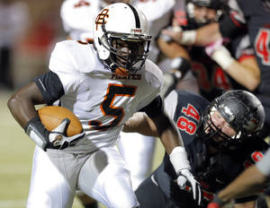 photo - Putnam City's Javone Knox gets by Westmoore's Soloman Vanover during the high school football game between Moore and Putnam City at Westmoore High School,  Thursday, Oct. 4, 2012. Photo by Sarah Phipps, The Oklahoman