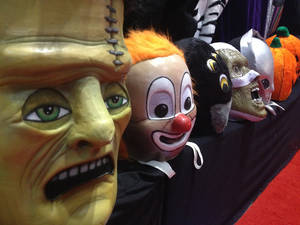 Photo - This photo taken Wednesday, Nov. 20, 2013 shows a row of masks for sale at the International Association of Amusement Parks and Attractions annual trade show in Orlando, Fla. The event is the largest of its kind in the theme and amusement park industry. (AP Photo/Tamara Lush)