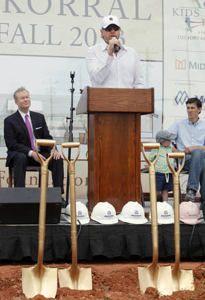Photo - Mayor Mick Cornett looks on as Toby Keith speaks during groundbreaking ceremonies for the OK Kids Korral, to be built by the Toby Keith Foundation at NE 8 and Laird, in Oklahoma City Friday, May 18, 2012. Photo by Paul B. Southerland, The Oklahoman