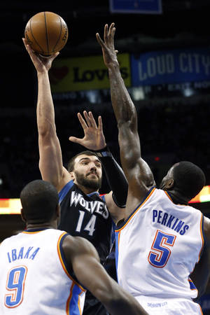photo - Minnesota Timberwolves center Nikola Pekovic (14) shoots in front of Oklahoma City Thunder forward Serge Ibaka (9) and center Kendrick Perkins (5) in the first quarter of an NBA basketball game in Oklahoma City, Wednesday, Jan. 9, 2013. (AP Photo/Sue Ogrocki)