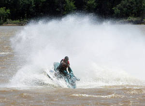 Photo - Amere Wright makes a sharp turn on a personal water craft at Lake Arcadia in Edmond, OK, Saturday, May 19, 2012,  By Paul Hellstern, The Oklahoman