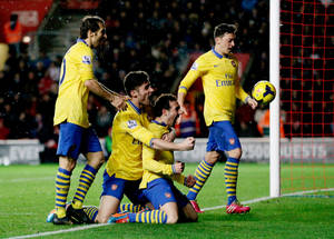 Photo - Arsenal's Santi Cazorla, third right, celebrates his goal with, from left, Mathieu Flamini, Olivier Giroud and Mesut Ozil during the English Premier League soccer match between Southampton and Arsenal at St Mary's stadium in Southampton, Tuesday, Jan. 28, 2014.  (AP Photo/Matt Dunham)
