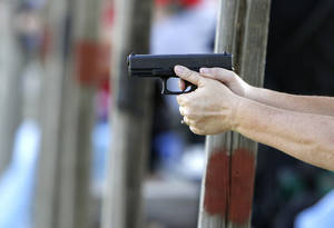 Photo - A woman shoots a handgun during the annual Women's Only Fun Shoot at the Oklahoma City Gun Club north of Arcadia, OK, Saturday, September 7, 2013,  Photo by Paul Hellstern, The Oklahoman