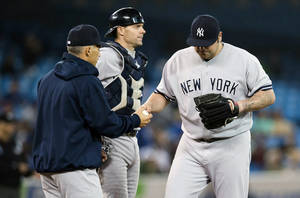 Photo - New York Yankees' Joba Chamberlain walks off the mound after being pulled by manger Joe Girardi, left, as catcher Chris Stewart, center, looks on against the Toronto Blue Jays during the seventh inning of a baseball game in Toronto, Thursday, Sept. 19, 2013. (AP Photo/The Canadian Press, Mark Blinch)