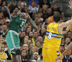 Photo - Boston Celtics forward Kevin Garnett, left, throws the ball at Denver Nuggets forward Danilo Gallinari, of Italy, in an efort to keep the ball in play late in the fourth quarter of the Nuggets' 97-90 victory in an NBA basketball game in Denver on Tuesday, Feb. 19, 2013. (AP Photo/David Zalubowski)