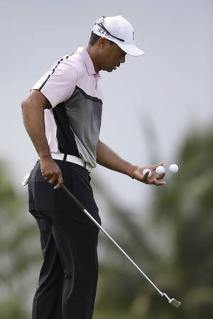 Photo - Golfer Tiger Woods gathers his balls as he putts on the fifth hole during a practice round in the Cadillac Championship golf tournament, Wednesday, March 5, 2014 in Doral, Fla. Three days after he withdrew in the middle of the final round at the Honda Classic with lower back pain, Woods returned to work at the Cadillac Championship by saying he feels better after a few days of constant treatment, and that he was good enough to try to defend his title. (AP Photo/Wilfredo Lee)