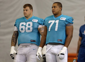 Photo - FILE - In this July 24, 2013 file photo, Miami Dolphins guard Richie Incognito (68) and tackle Jonathan Martin (71) stand on the field during an NFL football practice in Davie, Fla. Two people familiar with the situation say suspended Dolphins guard Incognito sent text messages to teammate Jonathan Martin that were racist and threatening. The people spoke to The Associated Press on condition of anonymity because the Dolphins and NFL haven't disclosed the nature of the misconduct that led to Incognito's suspension. Martin remained absent from practice Monday, Nov. 4, 2013, one week after he suddenly left the team.  (AP Photo/Lynne Sladky, File)