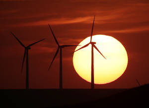 Photo - In this Aug. 23, 2013 file photo wind turbines are silhouetted by the setting sun as they produce electricity near Beaumont, Kan. The plains of Kansas could be a treasure trove in the nation's growing effort to harness clean energy. But a major proposal to move wind-generated electricity from Kansas to the East is running into a roadblock: Farmers who don't want high-power transmission lines on their land. (AP Photo/Charlie Riedel, File)