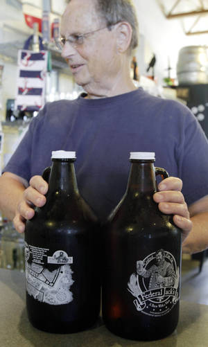Photo -   In this Monday, Sept. 26, 2011 photo, a customer sets two Federal Jack's growlers on a counter to purchase in Kennebunk, Maine. Around the country, hundreds of brewpubs, breweries and even grocery stores are cashing in on the growing popularity of growlers. (AP Photo/Pat Wellenbach)