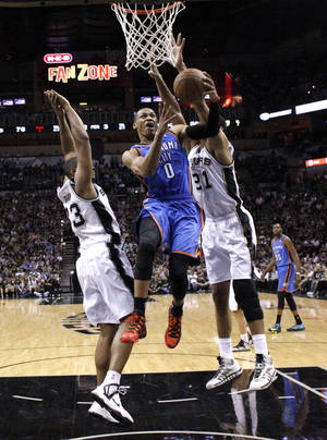Photo - Oklahoma City's Russell Westbrook (0) shoots a lay up in between San Antonio's Boris Diaw (33) and San Antonio's Tim Duncan (21) during Game 2 of the Western Conference Finals in the NBA playoffs between the Oklahoma City Thunder and the San Antonio Spurs at the AT&T Center in San Antonio, Wednesday, May 21, 2014. Photo by Sarah Phipps