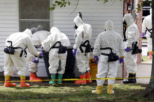 Photo - FILE - In this Friday, April 19, 2013 file photo, federal agents wearing hazardous material suits inspect a trash can outside the house of Paul Kevin Curtis in Corinth, Miss. Curtis is in custody under the suspicion of sending letters covered in ricin to U.S. President Barack Obama and U.S. Sen. Roger Wicker, R-Miss. Event after nail-biting event, America was rocked this week, in rare and frightening ways, with what felt like an unremitting series of tragedies. (AP Photo/Rogelio V. Solis, File)